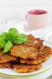 Kartoffelpfannkuchen und Schale Milch Lizenzfreies Stockbild
