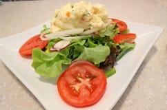 Kartoffelsalat auf einer weißen Platte Lizenzfreies Stockbild