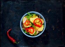 Kartoflana sałatka z bekonem, bogato przyprawiającym z wybranymi pikantność w błękitnym pucharze na rocznika metalu ośniedziałym  zdjęcia royalty free