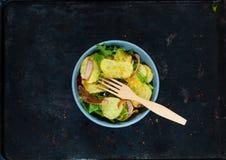 Kartoflana sałatka z bekonem, bogato przyprawiającym z wybranymi pikantność w błękitnym pucharze na rocznika metalu ośniedziałym  obrazy stock