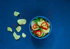 Kartoflana sałatka z bekonem, bogato przyprawiającym z wybranymi pikantność w błękitnym pucharze na błękitnym tle beton Odgórny w zdjęcia royalty free