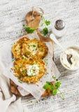 Kartoflani bliny lub latkes z śmietanką słuzyć na oliwnej tnącej desce nad białym drewnianym stołem Wieśniaka styl Obrazy Stock