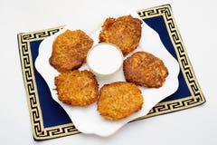 Kartoflani bliny z kwaśną śmietanką na białym talerzu Zdjęcia Royalty Free