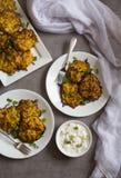 Kartoflani latkes blin w białych porcja talerzach z kwaśnej śmietanki opatrunkiem przy stroną przeciw popielatemu tłu obraz stock
