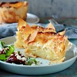 Kartoflany gratin piec w filo cieście, z crispy serową skorupą i z sałatką, arugula, suszący pomidory i ser, obrazy royalty free