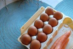 Karton frech Eier und Karotten in der Höchstansicht Stockfotografie