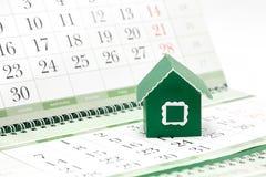 Karton groen huis op de achtergrond van de kalender Stock Afbeelding