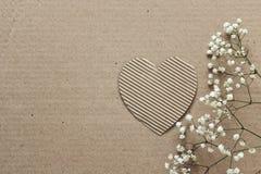 Kartonachtergrond met harten en kleine witte bloemen ruimte Royalty-vrije Stock Foto's