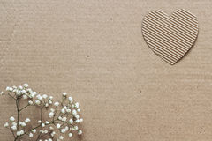 Kartonachtergrond met harten en kleine witte bloemen ruimte Stock Afbeelding