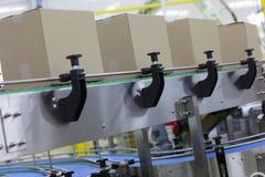 Kartondozen op transportband in fabriek stock afbeeldingen