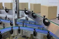 Kartondozen op transportband in fabriek stock foto's
