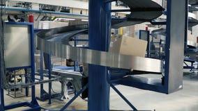 Kartondozen op transportband in fabriek klem Productielijn waarop de dozen zich in een spiraal bewegen royalty-vrije stock afbeelding