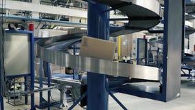 Kartondozen op transportband in fabriek klem Productielijn waarop de dozen zich in een spiraal bewegen stock video