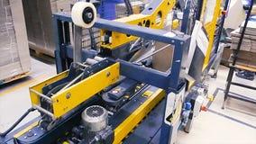 Kartondozen op transportband in fabriek klem Productielijn waarop de dozen zich in een spiraal bewegen stock afbeelding