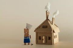 Kartonhuis met schoorsteen en witte rook Het karakter van de wasknijperchef-kok, gietlepel De ruimte van het exemplaar royalty-vrije stock afbeeldingen