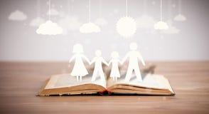 Kartonowe postacie rodzina na rozpieczętowanej książce Zdjęcia Stock