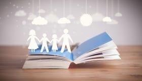 Kartonowe postacie rodzina na rozpieczętowanej książce Zdjęcie Stock