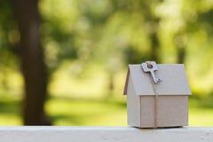 Kartonu dom z kluczem przeciw zielonemu bokeh Budynku, pożyczki, parapetówy, ubezpieczenia, nieruchomości lub kupienia nowy dom, Obraz Royalty Free