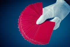 Karty i ręka odizolowywający na zmroku - błękitny tło Zdjęcie Stock