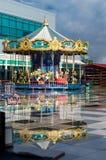 Karusell på en molnig dag med reflexion royaltyfri fotografi
