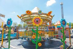 Karusellkedjor f?r barn i ljusa f?rger under en m?ssa i en italienare parkerar blomman formade ljus arkivbilder