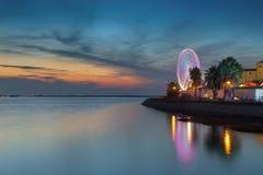 Karussell des angemessenen und großen Rades Auf einem Hintergrund des Seesonnenuntergangs Stockfoto