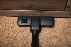 Karweien op tapijt, elektrische stofzuiger stock foto's