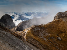 Karwendel mountain pass. Mountain pass seen from above, with mountains and clouds in the background, and hikers on the pass; colours of autumn, in the Bavarian Stock Images