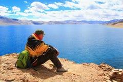 KARZOK LADAKH, INDIEN - 18 AUGUSTI 2015: Den oidentifierade mannen sitter på kusten av sjöTso Moriri och ser vattnet Fotografering för Bildbyråer