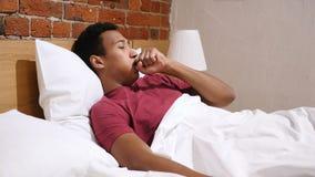 Kasłać Chorego Afrykańskiego mężczyzna lying on the beach w łóżku przy nocą zbiory wideo