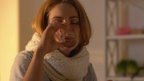 Kasłać kobiety pije syrop podczas grypowej wirusowej choroby w szaliku, traktowanie zbiory