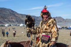 Kasachische traditionelle Kleidung Eagle Hunters, bei der Jagd zu den Hasen, die einen Steinadler auf seinem Arm halten Stockfotografie