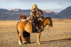 Kasachische traditionelle Kleidung Eagle Hunters, bei der Jagd zu den Hasen, die einen Steinadler halten Stockfotografie