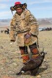 Kasachische traditionelle Kleidung Eagle Hunters, mit einem Steinadler auf seinem Arm während des jährlichen nationalen Wettbewer Lizenzfreies Stockfoto