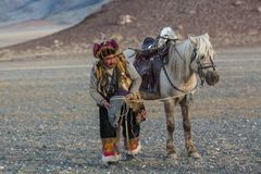 Kasachischer Eagle Hunter Berkutchi mit Pferd bei der Jagd zu den Hasen mit von Steinadlern Lizenzfreie Stockfotografie