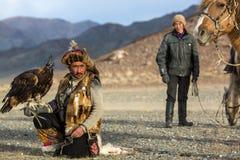 Kasachischer Eagle Hunter Berkutchi mit Pferd bei der Jagd zu den Hasen mit von Steinadlern auf seinen Armen Stockfoto