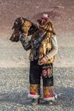 Kasachischer Eagle Hunter Berkutchi mit Pferd bei der Jagd zu den Hasen mit von Steinadlern auf seinen Armen Lizenzfreie Stockfotos
