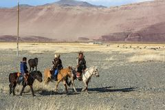 Kasachischer Eagle Hunter Berkutchi mit Pferd unterrichtet seine Tochter zur Jagd Lizenzfreie Stockfotografie