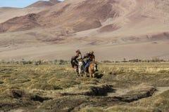 Kasachischer Eagle Hunter Berkutchi mit Pferd unterrichtet seine Tochter zur Jagd zu den Hasen mit von Steinadlern Lizenzfreie Stockfotos