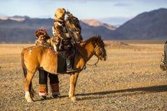 Kasachischer Eagle Hunter Berkutchi mit Pferd unterrichtet seine Tochter zur Jagd zu den Hasen mit von Steinadlern Lizenzfreies Stockfoto