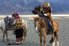 Kasachischer Eagle Hunter Berkutchi mit Pferd unterrichtet seine Tochter zur Jagd zu den Hasen mit von Steinadlern in den Bergen Stockfoto