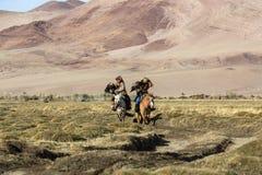 Kasachischer Eagle Hunter Berkutchi mit Pferd unterrichtet seine Tochter zur Jagd zu den Hasen mit von Steinadlern in den Bergen Stockfotos