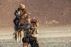 Kasachischer Eagle Hunter mit Pferd unterrichtet seine Tochter zur Jagd zu den Hasen mit von Steinadlern in den Bergen Lizenzfreie Stockbilder