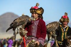 Kasachischer goldener Eagle Hunter an der traditionellen Kleidung, mit einem Steinadler auf seinem Arm Lizenzfreies Stockbild