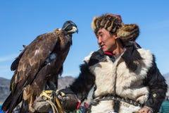 Kasachischer goldener Eagle Hunter an der traditionellen Kleidung, mit einem Steinadler auf seinem Arm Lizenzfreies Stockfoto
