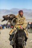 Kasachischer goldener Eagle Hunter an der traditionellen Kleidung, mit einem Steinadler auf seinem Arm während des jährlichen nat Stockfoto