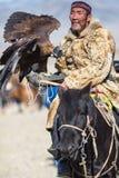 Kasachischer goldener Eagle Hunter an der traditionellen Kleidung, mit einem Steinadler auf seinem Arm während des jährlichen nat Stockfotografie