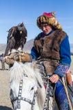 Kasachischer goldener Eagle Hunter an der traditionellen Kleidung, mit einem Steinadler auf seinem Arm während des jährlichen nat Stockfotos