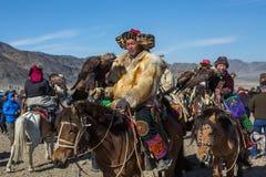 Kasachischer goldener Eagle Hunters an der traditionellen Kleidung, mit einem Steinadler auf seinem Arm Stockfotografie