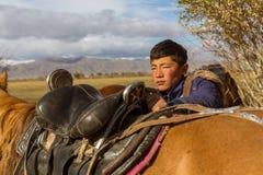 Kasachischer Jäger Berkutchi Eagle tun Sattelpferd In Bayan-Olgii wird Provinz bis 88,7% von den Kazakhs bevölkert Stockfoto
